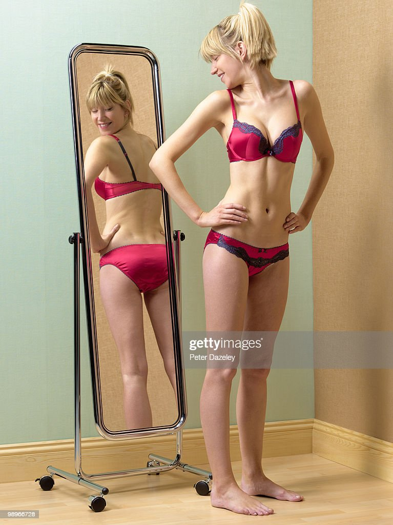 Anorexic Girl Looking At Bum In Mirror Stock Photo