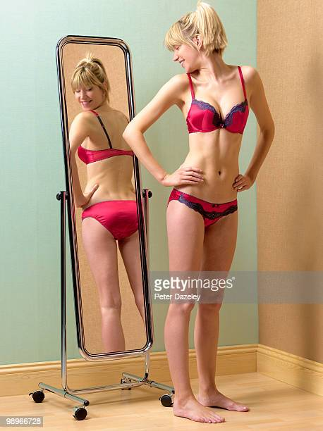 anorexic girl looking at bum in mirror - full length mirror stock photos and pictures