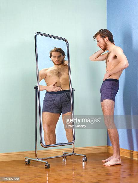 anorexic man looking at himself in mirror - anorexia nervosa imagens e fotografias de stock