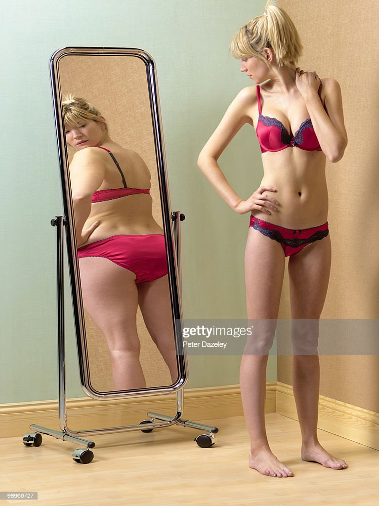 Anorexic woman looking at bum in mirror : Stock Photo