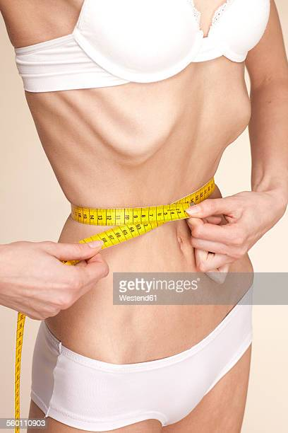 Anorexic young woman measuring her waist