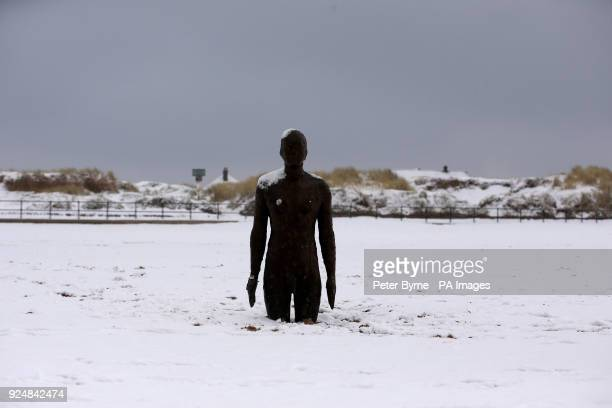 Another Place by Anthony Gormley surrounded by snow on Crosby Beech near Liverpool following heavy overnight snowfall which has caused disruption...