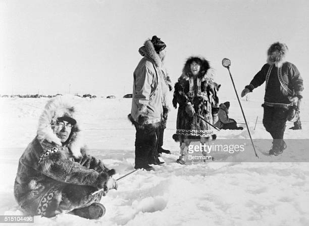 Another winter sport at Nome, Alaska, is fishing through the ice of the frozen Bering Sea for tomcod, Eskimo couple shows guests how to 'jig' for the...