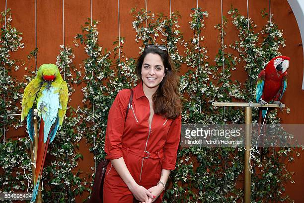 Anouchka Delon standing between parrots Arthur and Zoe attend the 2016 French Tennis Open Day Six at Roland Garros on May 27 2016 in Paris France