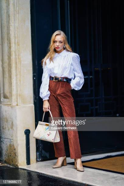 Anouchka Gauthier wears earrings, a white ruffled shirt with floral embroidery, a leather belt, brown pants with printed polka dots, a white leather...