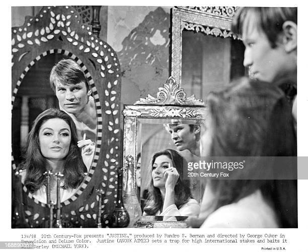 Anouk Aimée looks at herself in a mirror with Michael York in a scene from the film 'Justine' 1969