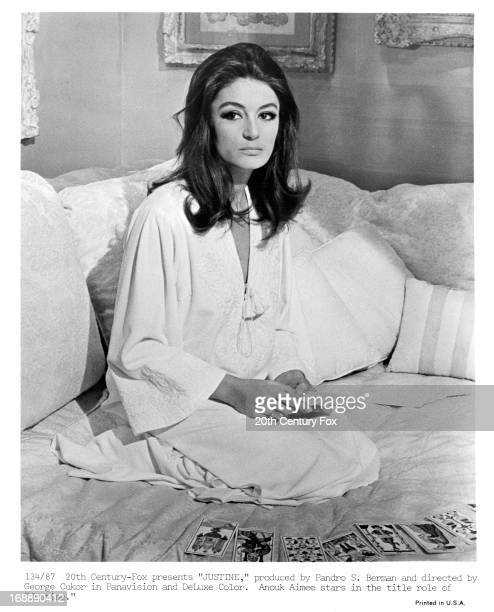 Anouk Aimée reads tarot cards in a scene from the film 'Justine', 1969.