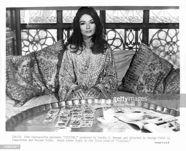 Anouk Aimee sitting before table full of cards in a scene from the film 'Justine', 1969.