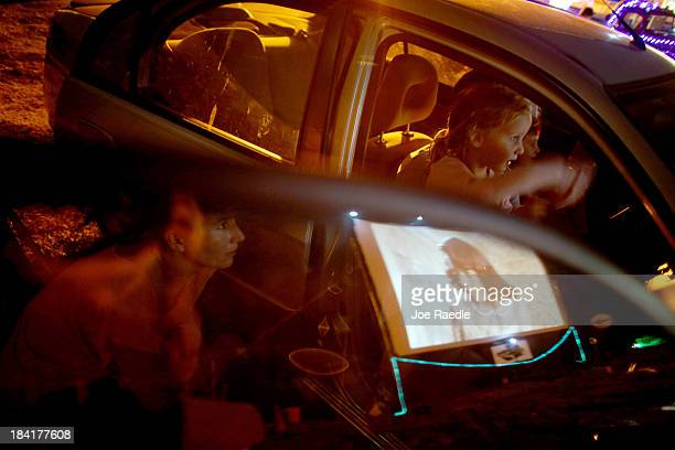 Anouska Greene Peyton Greene and Jeff Greene watch 'Back to the Future' at The Blue Starlite Mini Urban DriveIn on October 11 2013 in Miami Florida...