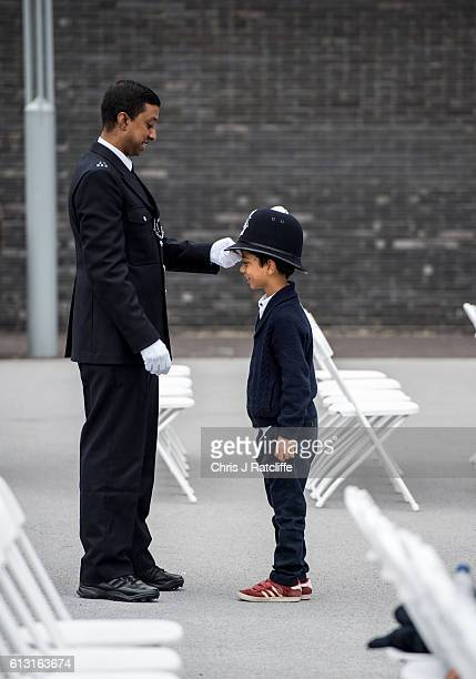 Anowarul Hoque puts his police hat on his son Jamal Hoque before the start of the Metropolitan Police 'Passing Out Parade' outside Peel House at...