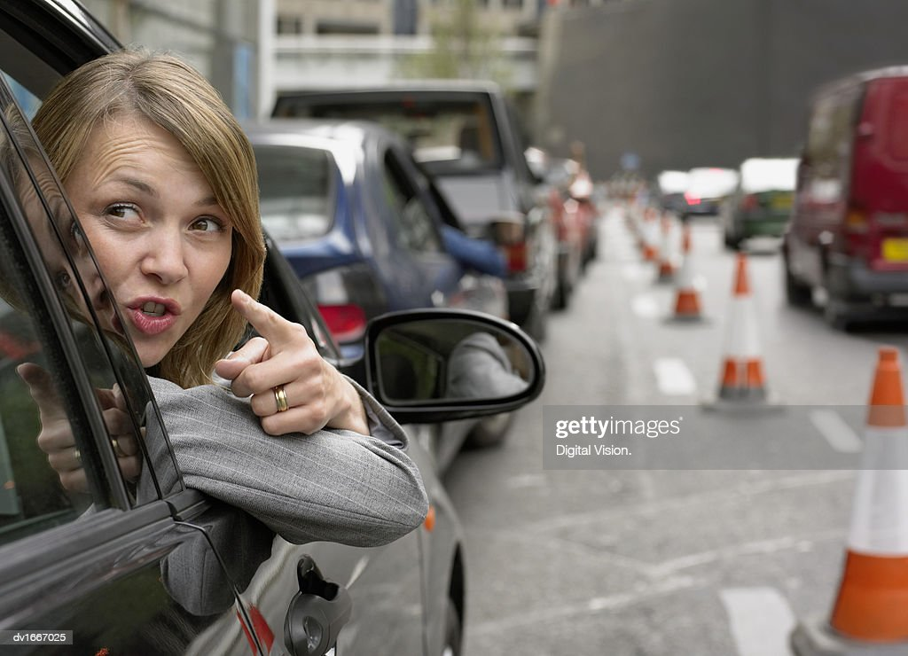 Anoyed Woman Looking Out Her Car Window Pointing : Stock Photo