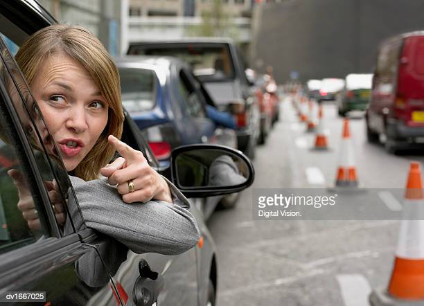 Anoyed Woman Looking Out Her Car Window Pointing