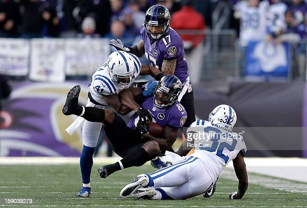 Anquan Boldin of the Baltimore Ravens catches a pass in the third quarter against Antoine Bethea and Cassius Vaughn of the Indianapolis Colts during...