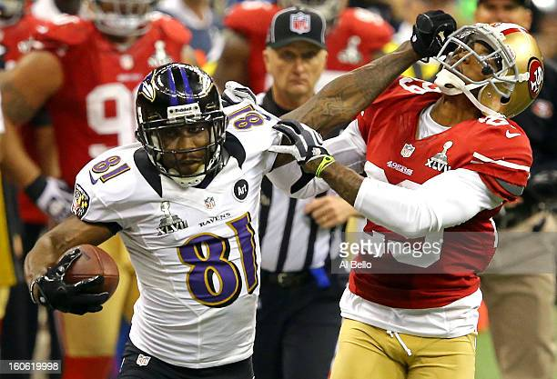Anquan Boldin of the Baltimore Ravens runs with the ball and stiff arms Chris Culliver of the San Francisco 49ers after catching a pass in the second...