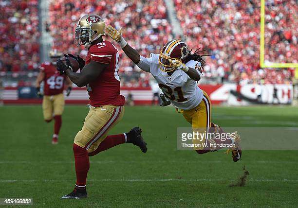 Anquan Boldin of the San Francisco 49ers runs the ball to score the first touchdown as Brandon Meriweather of the Washington Redskins tries to make...