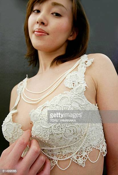 Anri Takao of Triumph International Japan displays a 'Pearl Bra' studded with pearls and decorated with antique laces at the opening of its luxury...