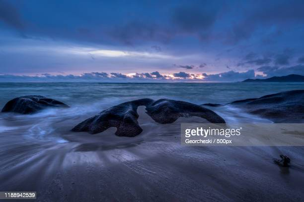 anse source dargent beach at dramatic dusk, la digue, seychelles - la digue island stock pictures, royalty-free photos & images