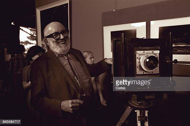 Ansel Adams at a party celebrating the fortieth anniversary of his photograph 'Moonrise Over Hernandez NM' He stands next to his viewfinder camera
