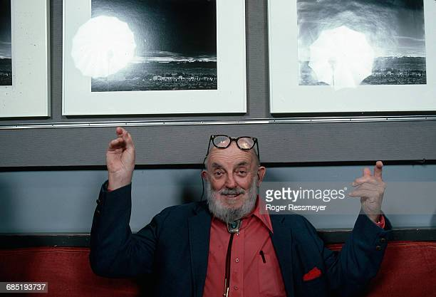 Ansel Adams sits on a couch in his house and points to two of his photographs where they hang on the wall