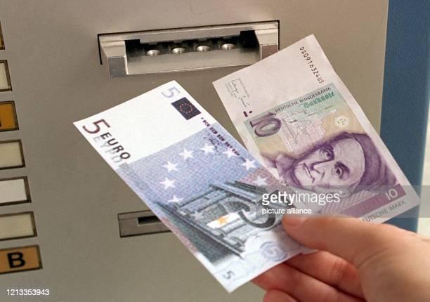 Ansicht eines Zehnmarkscheins und des Imitats eines Fünfeuroscheins vor dem Geldschlitz eines Fahrkartenautomaten . Für die neue Währung müssen in...