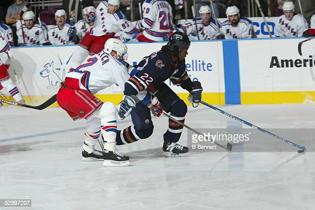 Anson Carter of the Edmonton Oilers skates with the puck as Brian Leetch of the New York Rangers defends circa 2003 at the Madison Square Garden in...