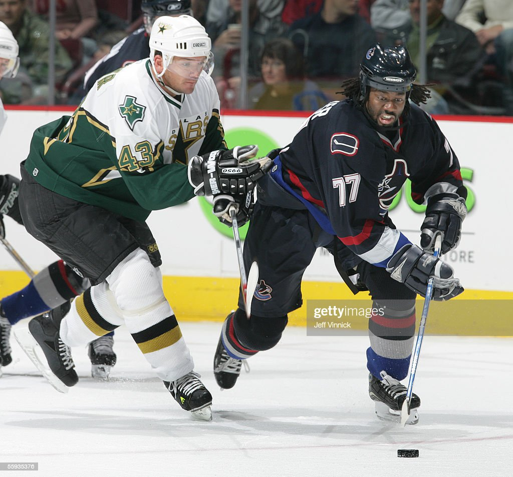 Anson Carter #77 of the Vancouver Canucks carries the puck against Philippe Boucher #43 of the Dallas Stars at General Motors Place on October 16, 2005 in Vancouver, Canada. The Canucks defeated the Stars 5-2.