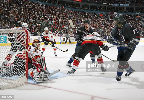 Anson Carter of the Vancouver Canucks shoots the puck past goaltender Miikka Kiprusoff of the Calgary Flames during their NHL game at General Motors...