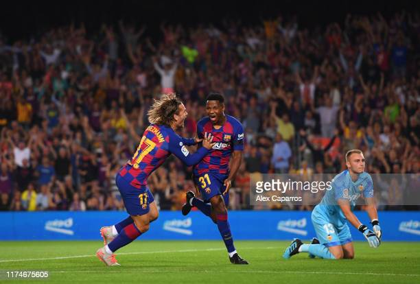 Anssumane Fati of Barcelona celebrates after scoring his team's first goal with Antoine Griezmann as Jasper Cillessen of Valencia looks...