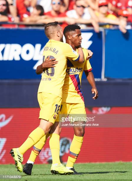 Anssumane Fati of FC Barcelona celebrates with teammate Jordi Alba after scoring the first goal of his team during the Liga match between CA Osasuna...