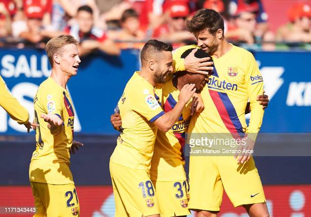 Anssumane Fati of FC Barcelona celebrates with teammates Jordi Alba and Gerard Pique after scoring the first goal of his team during the Liga match...
