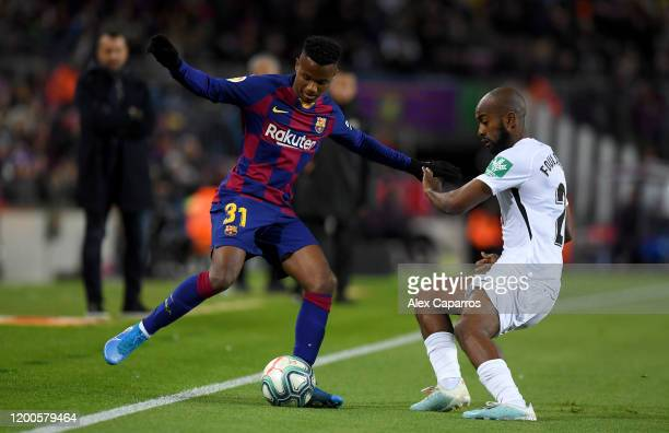 Anssumane Fati of FC Barcelona is challenged by Dimitri Foulquier of Granada CF during the La Liga match between FC Barcelona and Granada CF at Camp...