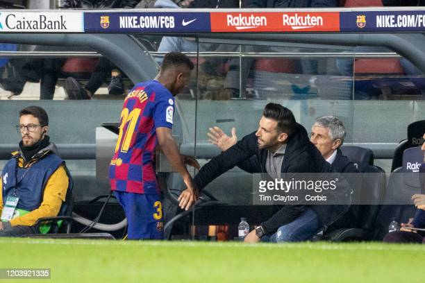 Ansu Fati of Barcelona is congratulated by Quique Setien head coach of Barcelona and assistant coach Eder Sarabia after being substituted late in the...