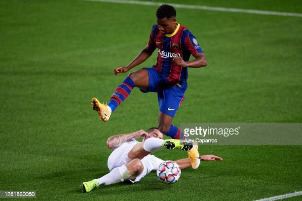 Ansu Fati of FC Barcelona is challenged by Endre Botka of Ferencvaros Budapest during the UEFA Champions League Group G stage match between FC...