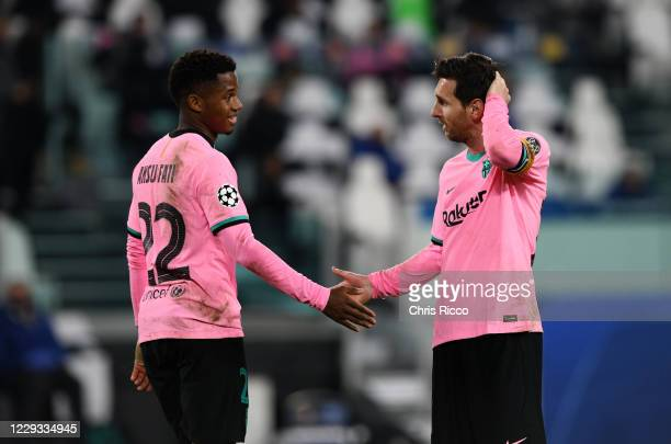 Ansu Fati of FC Barcelona shakes hands with Lionel Messi during the UEFA Champions League Group G stage match between Juventus and FC Barcelona at...