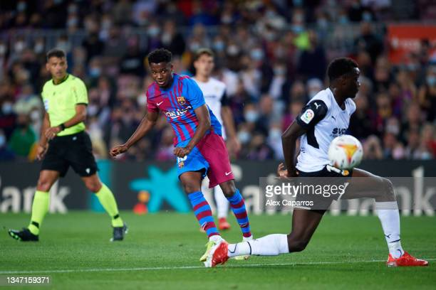 Ansu Fati of FC Barcelona shoots past Mouctar Diakhaby of Valencia CF to score his team's first goal during the LaLiga Santander match between FC...