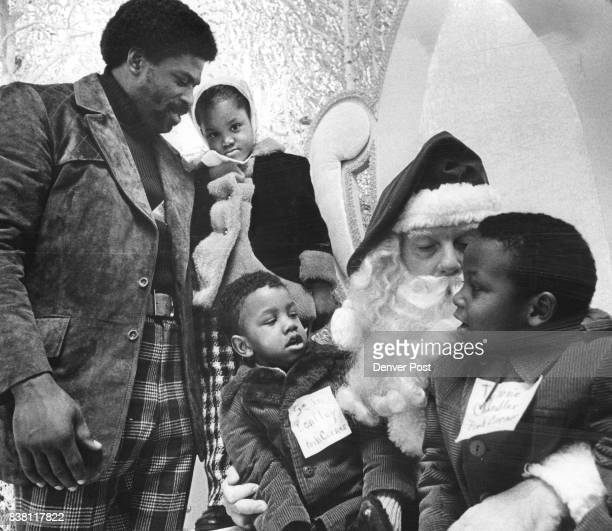 DEC 10 1972 DEC 12 1972 anta Claus whispers into Tyrone Chandler's ear right while Sean Bentley listens Standing are boxer Ron Lyle and Amy Dooley...