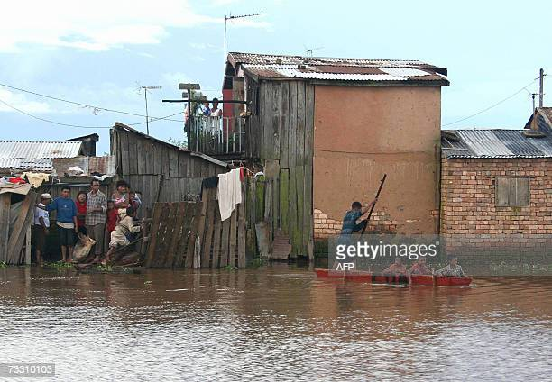 Antananarivo, MADAGASCAR: A group of stranded Madagascans watch as a man uses a dug-out canoe to cross a flooded section 10 February 2007 in...