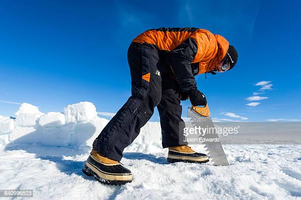 Antarctic base staff cutting ice bricks to make a kitchen wall on the sea ice during a survival course.