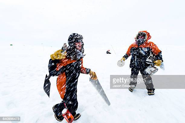 Antarctic base staff packing survival gear on the sea ice during a snow storm.