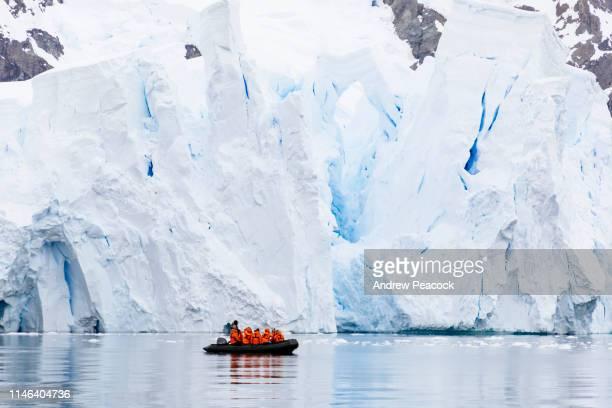 os turistas antárcticos visitam uma geleira pelo barco pequeno - bote inflável - fotografias e filmes do acervo