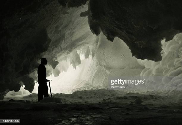 Interior of ice cave about 10 miles from McMurdo Station A man with an icepick stands there Undated photograph