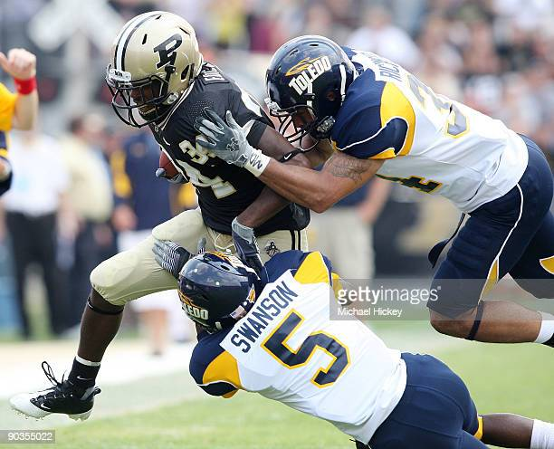 Antavian Edison of the Purdue Boilermakers is tackled by members of the Toledo Rockets at Ross-Ade Stadium on September 5, 2009 in West Lafayette,...