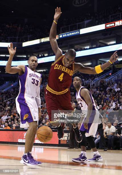 Antawn Jamison of the Cleveland Cavaliers loses the ball as he drives past Grant Hill and Michael Redd of the Phoenix Suns during the NBA game at US...