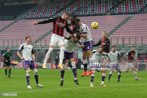 Ante Rebic and Franck Kessie of AC Milan contest for an aerial ball with Cristiano Biraghi and Nikola Milenkovic of ACF Fiorentina during the Serie A...