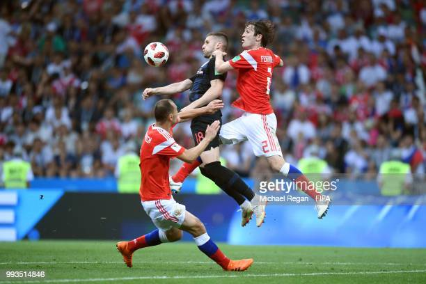 Ante Rebic of Croatia is challenged by Sergey Ignashevich of Russia and Mario Fernandes of Russia during the 2018 FIFA World Cup Russia Quarter Final...