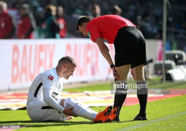 Ante Rebic of Frankfurt on the ground and Referee Felix Zwayer looks on during the Bundesliga match between Werder Bremen and Eintracht Frankfurt at...