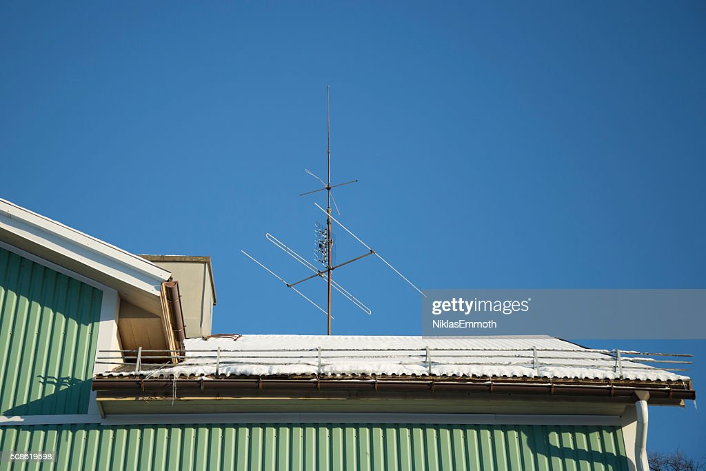 TV Antenna on Snow Covered Roof : Stock Photo