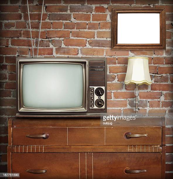 Antennae television sitting on dresser with antique lamp