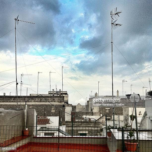 Antennas On Roof Of Houses Against Cloudy Sky