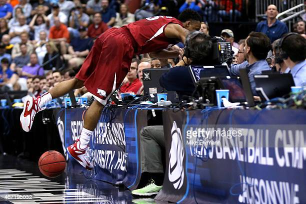 Anthlon Bell of the Arkansas Razorbacks dives over the media tables as after he chased down a loose ball against the North Carolina Tar Heels in the...